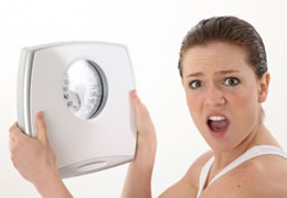 Picture of a woman holding weight scale