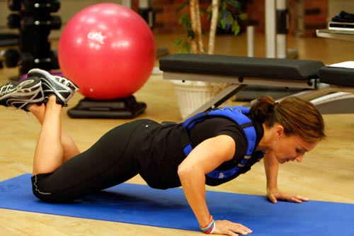Cathe doing a Bent Leg Pushup with a Fitness by Cathe weighted vest.