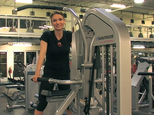 Cathe on a Nautilus Gravitron (assisted pull up machine)