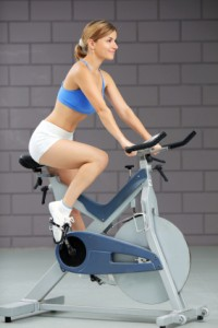 Girl training on exercise bike at the gym