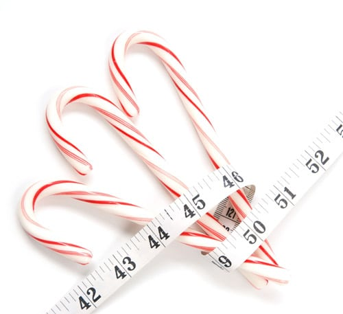 Three Candy Canes wrapped in a measuring tape reminding us of holiday weight gain that usually happens this time of year.