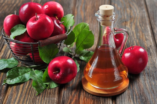 A bowl of red apples and a bottle of apple cider vinegar on a wooden table.