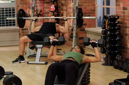 Robert and Denise lifting heavy weights after taking their one-rep max test during Cathe's STS workout series.
