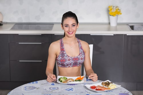A fit girl eating a selection of plant-based protein and animal protein.