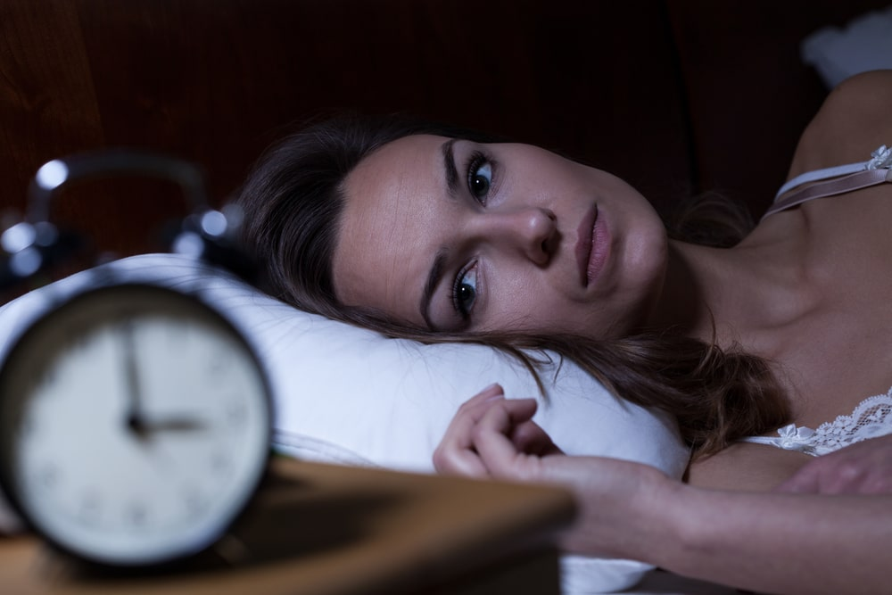 A woman in bed can't fall asleep. Is it normal to have sleep problems as you get older?