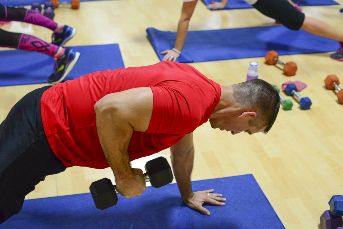 Image of a male exerciser doing a plank kickback with a dumbbell during a Cathe Friedrich road trip. It's important to devote time to strength and power training and to avoid Imbalanced exercise training.