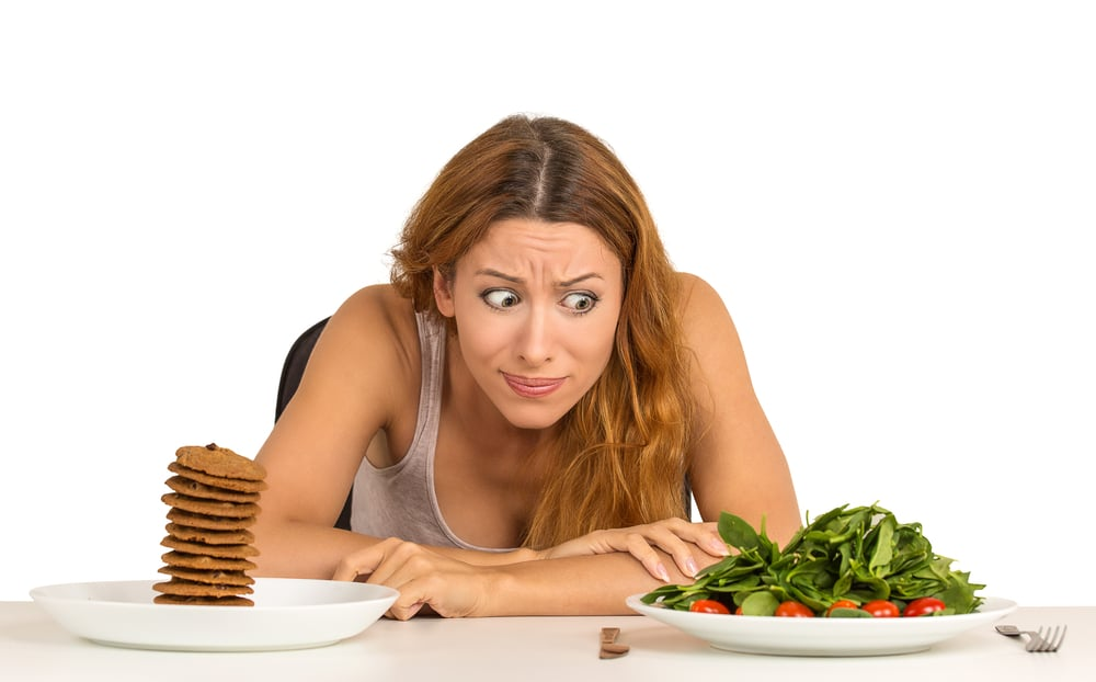 Young woman deciding whether to eat healthy food or sweet cookies loaded with unhealthy carbs