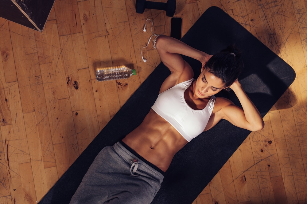 A woman on an exercise mat doing crunches as part of her abdominal training.