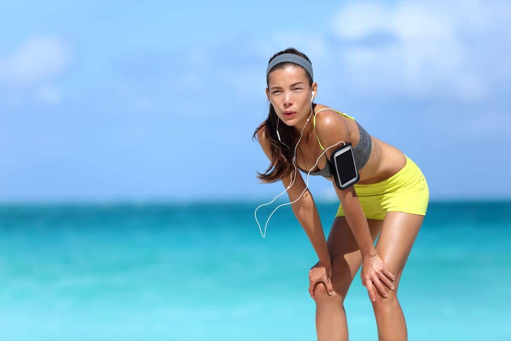A woman having a rough time running on the beach exercising in the heat