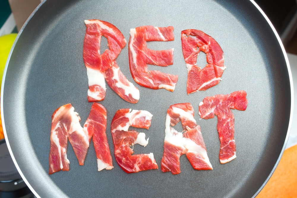 The inscription RED MEAT on the teflon frying pan lined with pieces of raw meat