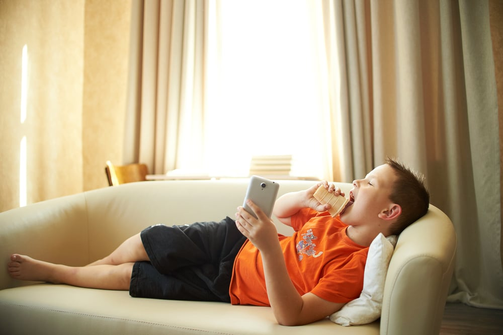 A young boy is lying on the couch playing with the phone in the room in an orange shirt is eating ice cream. Childhood inactivity is now a public health hazard. Motivate your kids to put away technology and get off the couch.