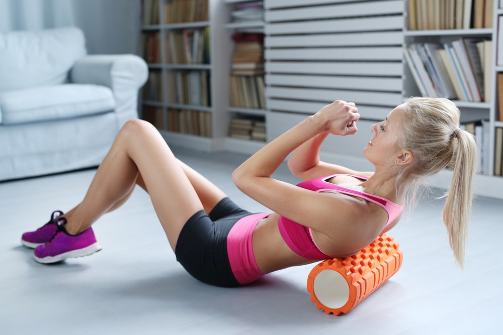 A woman working on her sore back and shoulders by foam rolling
