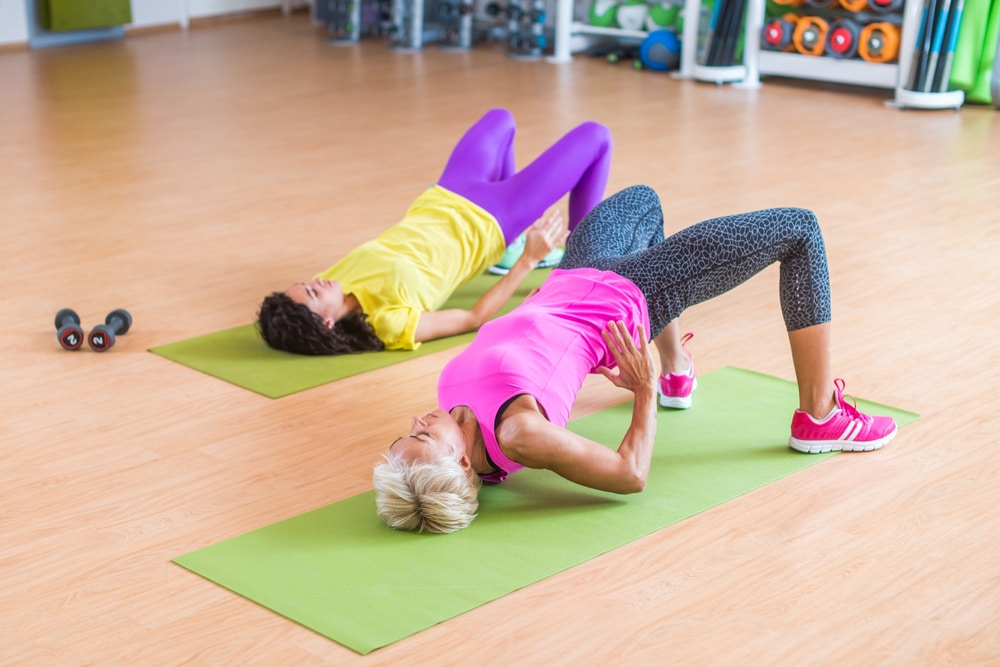 Two exercisers doing glute bridges working their gluteal muscles