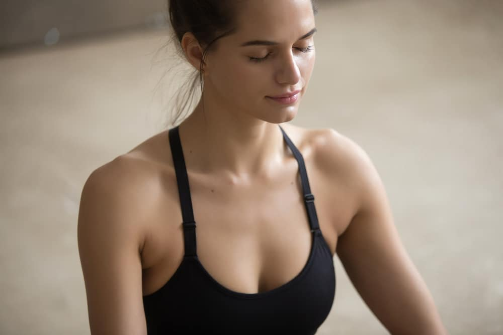 A young woman using meditation to get ready for strength training