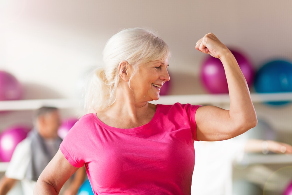 image of fit elderly woman proudly striking a bicep pose showing that strength training not only builds muscle, but also improves your metabolism.