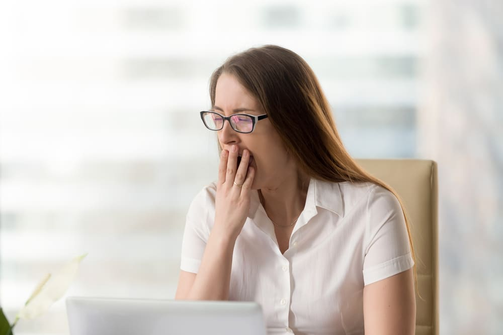 A woman at work yawning while sitting in her chair at her desk with her computer. Lear about 6 habits that can make you feel tired.