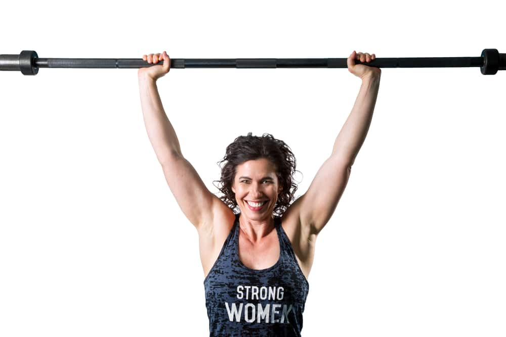A happy and confident, muscular female trainer easily holds an unloaded barbell over her head getting ready to start her hypertrophy training