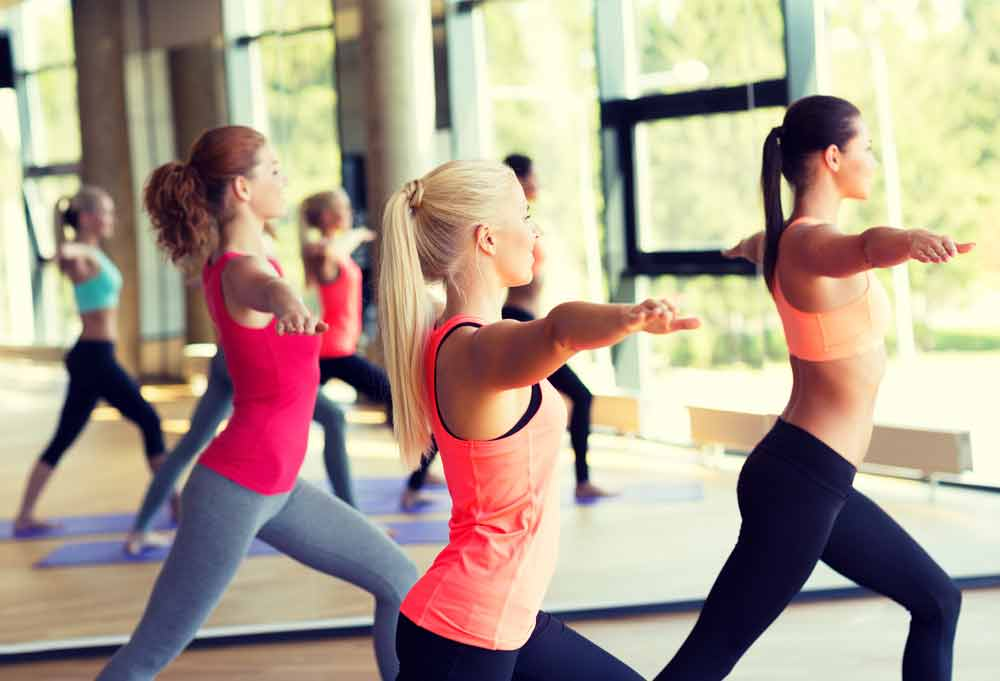 image of female exercisers working out doing yoga and aerobic exercise