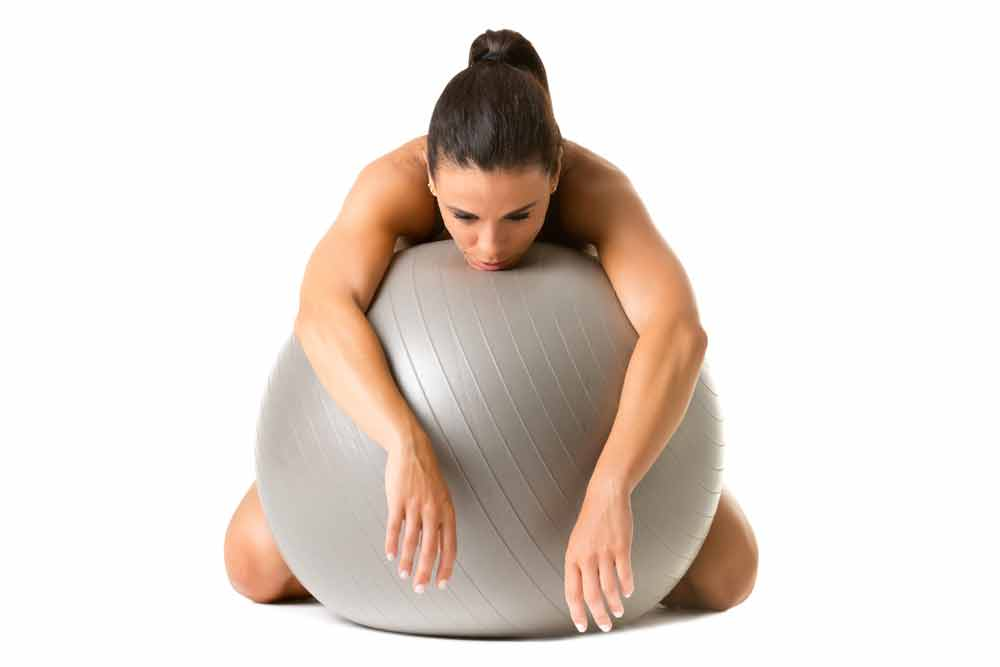 image of tired female exerciser resting on a stability ball