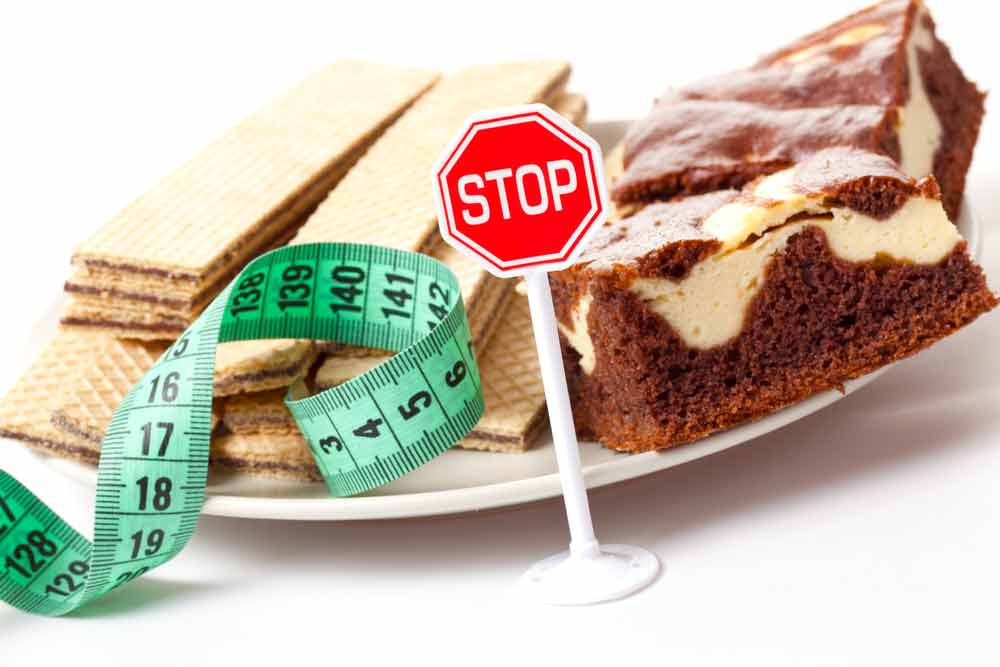 image of desert foods high in sugar and a stop sign suggesting you learn to stop your sugar cravings