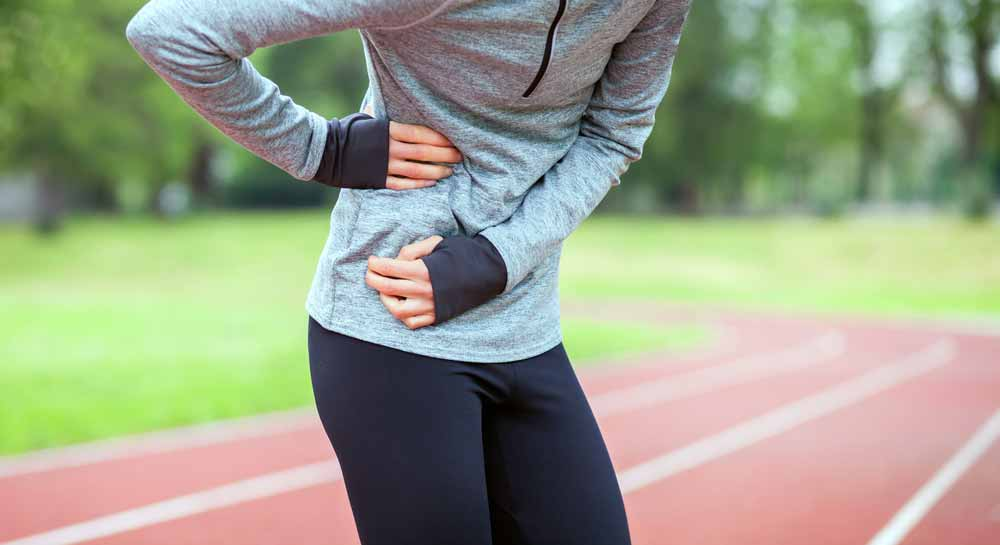 image of female runner in pain from side stiches