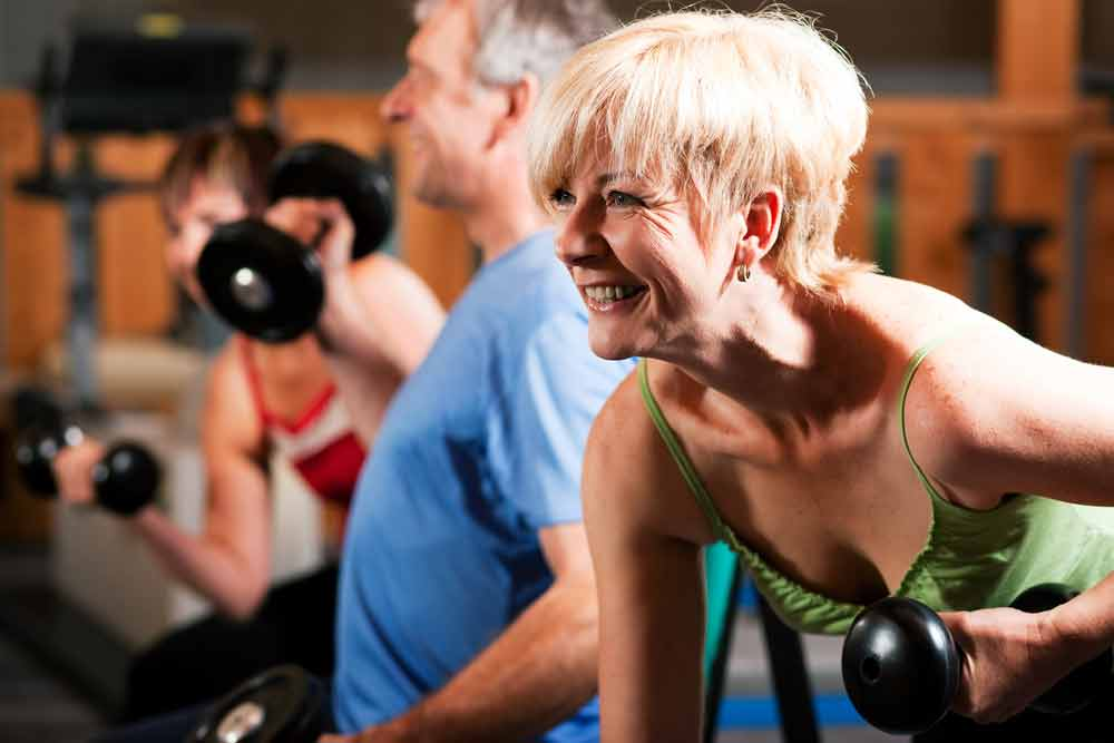 """Image of two senior exercisers working out. We're all interested in slowing the aging process as well as lowering the risk of age-related health problems. Strength training helps you do that! Here are five, """"old age"""" health problems that strength training lowers the risk of."""