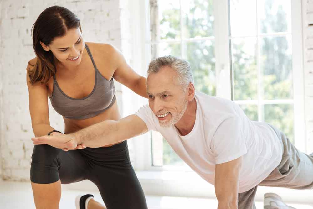 image of young female trainer supervising a senior male exerciser