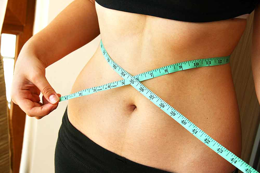 image of woman's waist with a measuring tape around it checking to see if she has had any weight regain