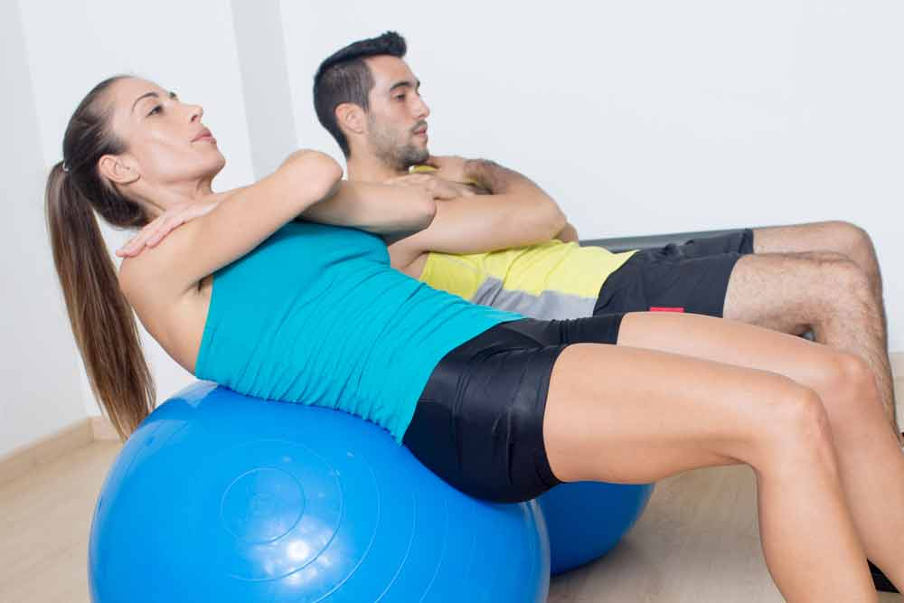 image of a woman and a man doing abdominal crunches on a blue stability ball