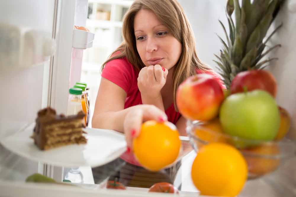 image of a woman trying to decide between eating something good or bad.