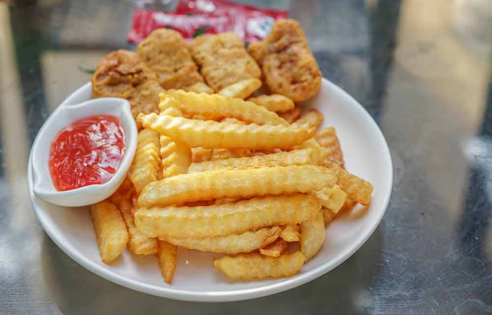 image showing unhealthy processed foods on a plate with fries, chicken nuggets and ketchup