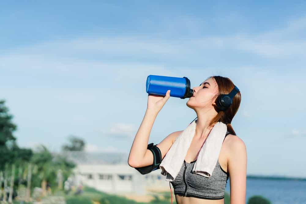 image of woman drinking an exercise recovery diet drink after working out