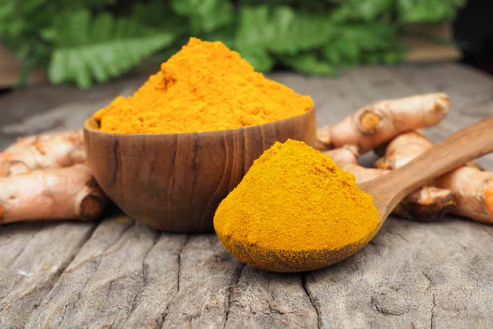image of a bowl and sppon full of Tumeric