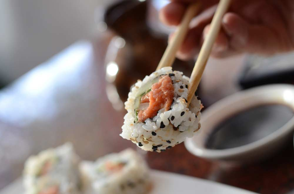 image of chopsticks holding Sushi. Chopsticks and focusing on your meal helps to prevent mindless overeating