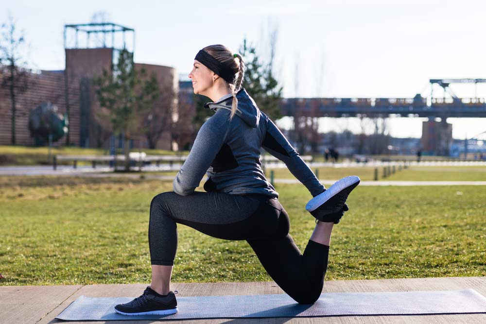 image of a woman doing a quadriceps stretch outside