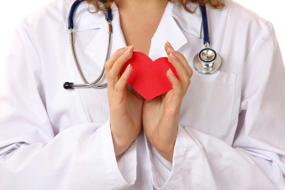 image of a woman doctor holding a red heart to bring attention to heart disease