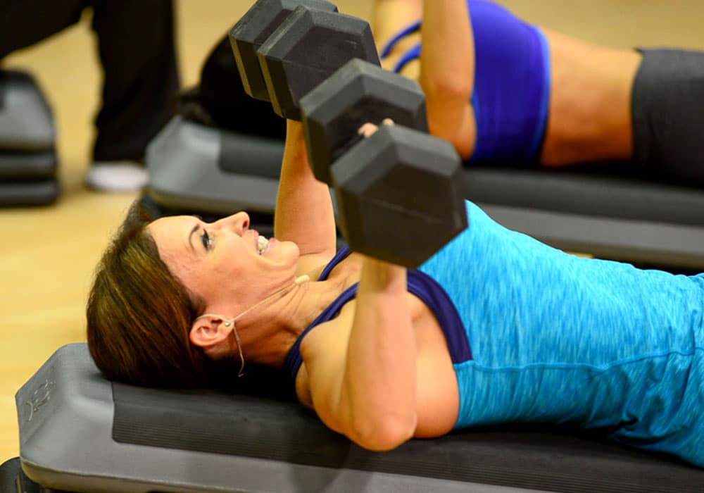 image of Cathe Friedrich doing a dumbbell chest press on a step