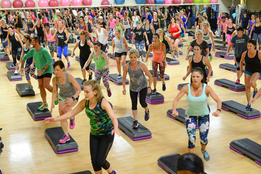 image of a large group of people of various ages working out doing a step aerobics class in a gym. Exercise has many benefits and may lower the risk of dying prematurely.