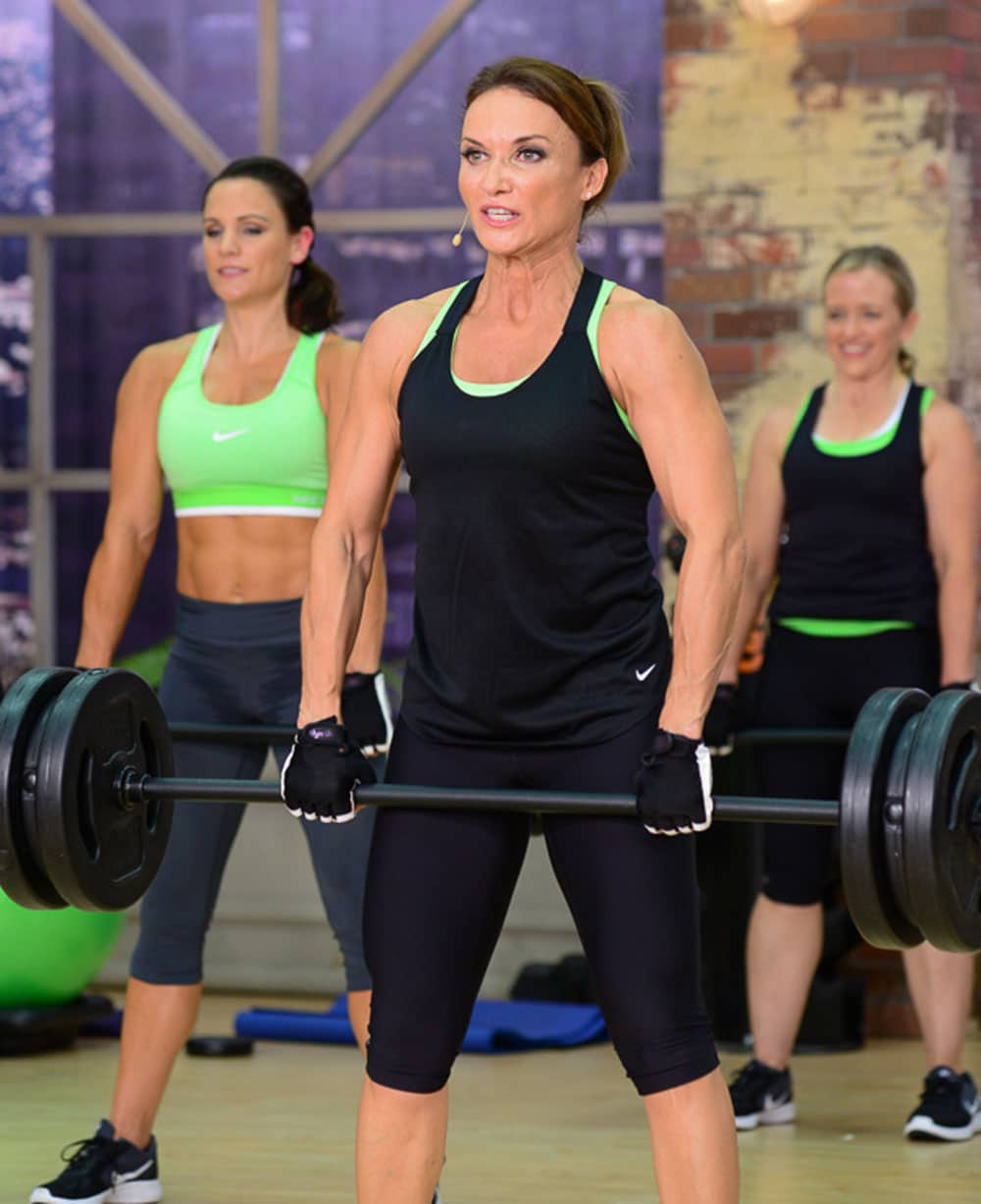 image of Cathe Friedrich doing a deadlift in Strong & Sweaty Total Body Giant Sets. A strong back helps to prevent back pain.