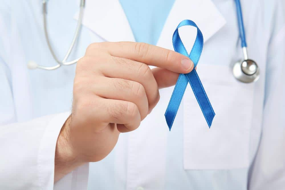 image of doctor holding blue ribbon, closeup. Cancer awareness concept
