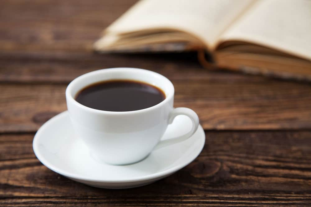 image of a Cup of coffee on a wooden table. Can drinking coffee boost your metabolism?