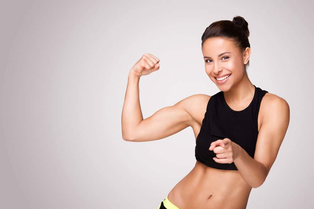 image of a young woman showing her biceps muscles