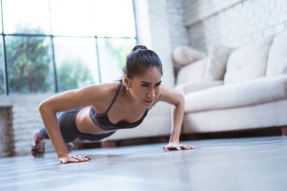 image of a woman doing a push up in her living room