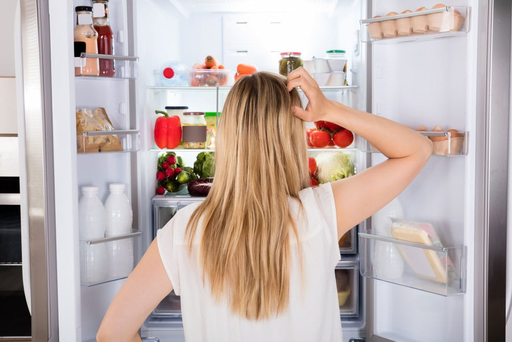 image of a young woman looking inside her refrigerator because she is hungry and not full after a meal