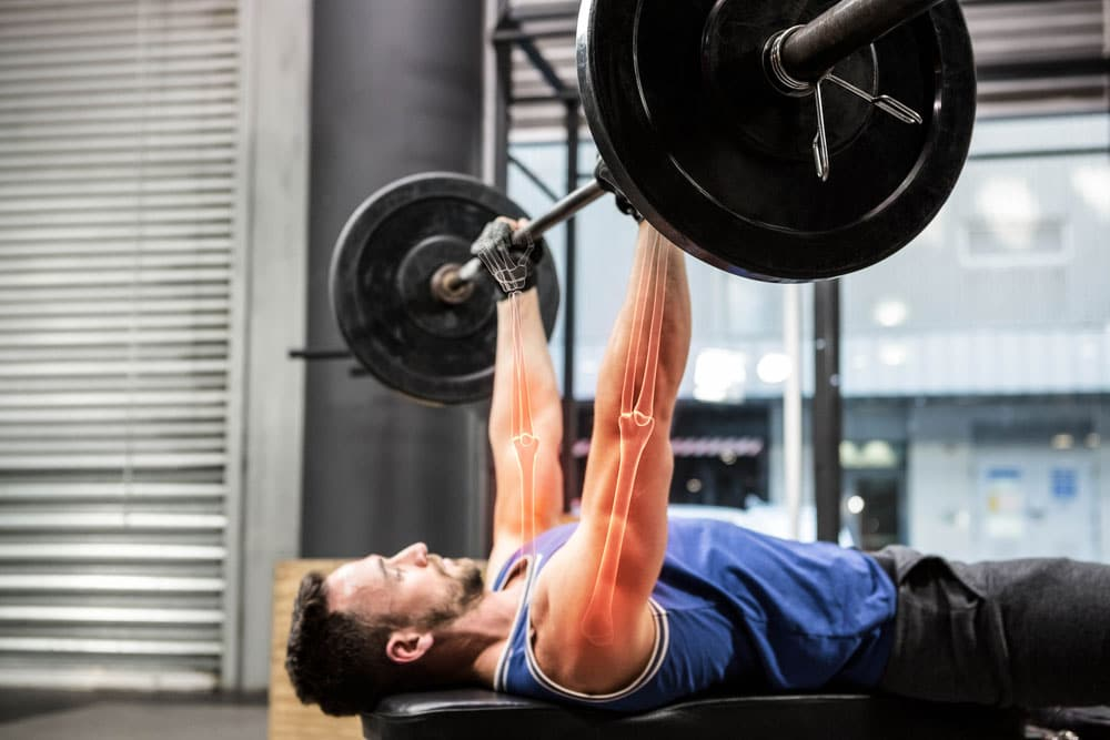 image of an athlete exercising doing a barbell bench press at a gym. Resistance training is great for bone health.