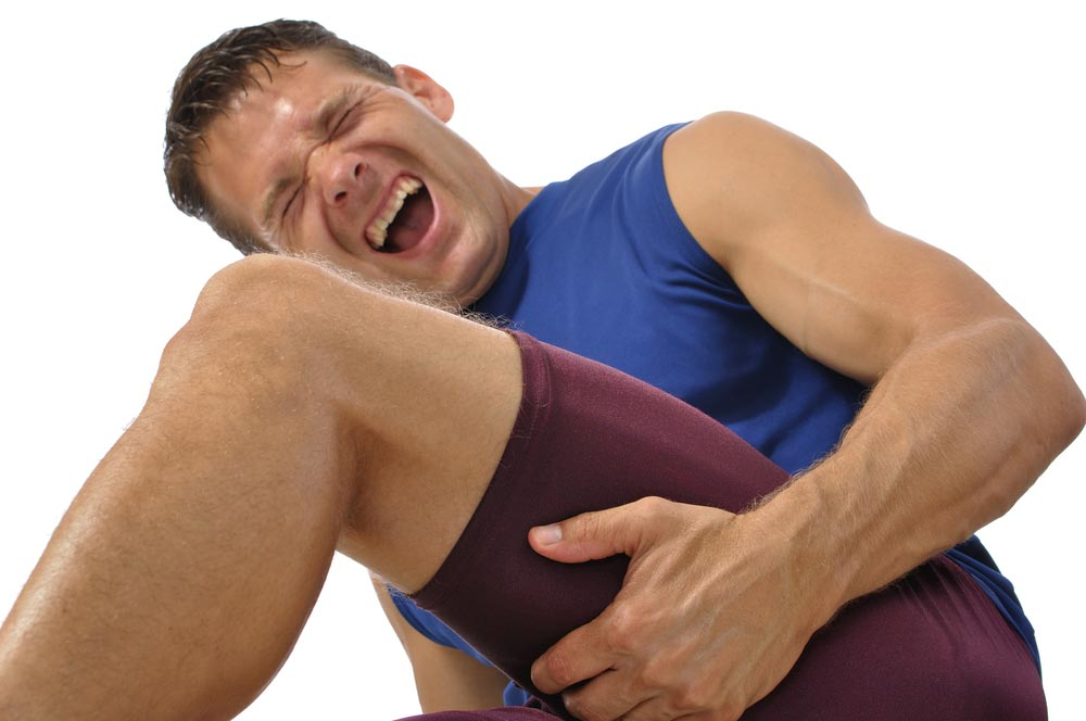 image of a male athlete clutching his hamstring in excruciating pain on white background