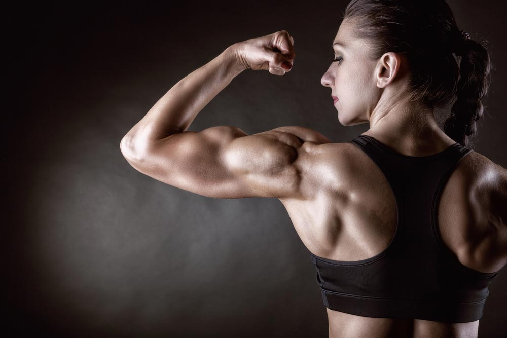 image of an Athletic young woman showing muscles of the back , shoulders and arms on a black background