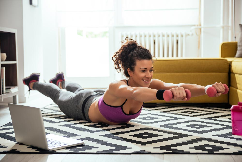image of a young woman exercising at home her living room not letting mental blocks stop her from working out