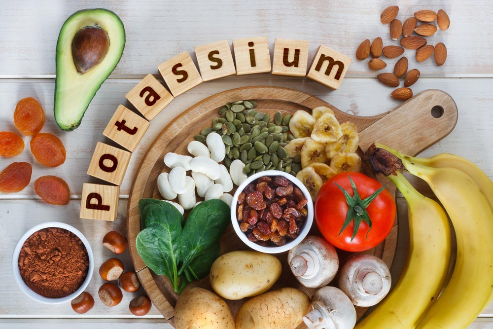 image of Potassium Food Sources as dried apricots, raisins, avocado, cocoa, bean, pumpkin seeds, dried banana, potatoes, tomatoes, spinach, mushrooms, fresh banana, hazelnuts, almonds.