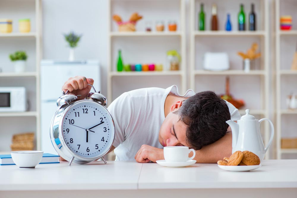 image of a man with alarm clock falling asleep at breakfast